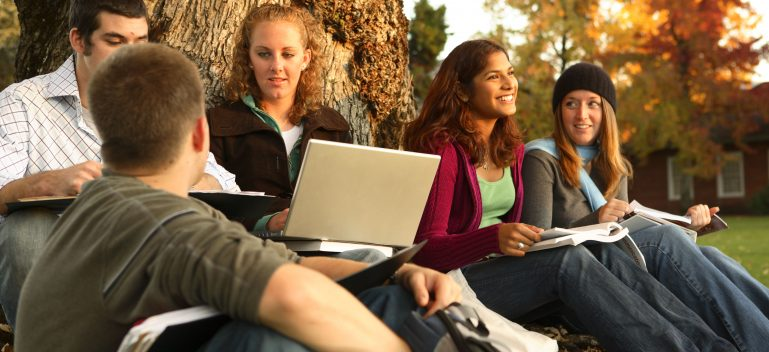 Group of college students outdoors studying.