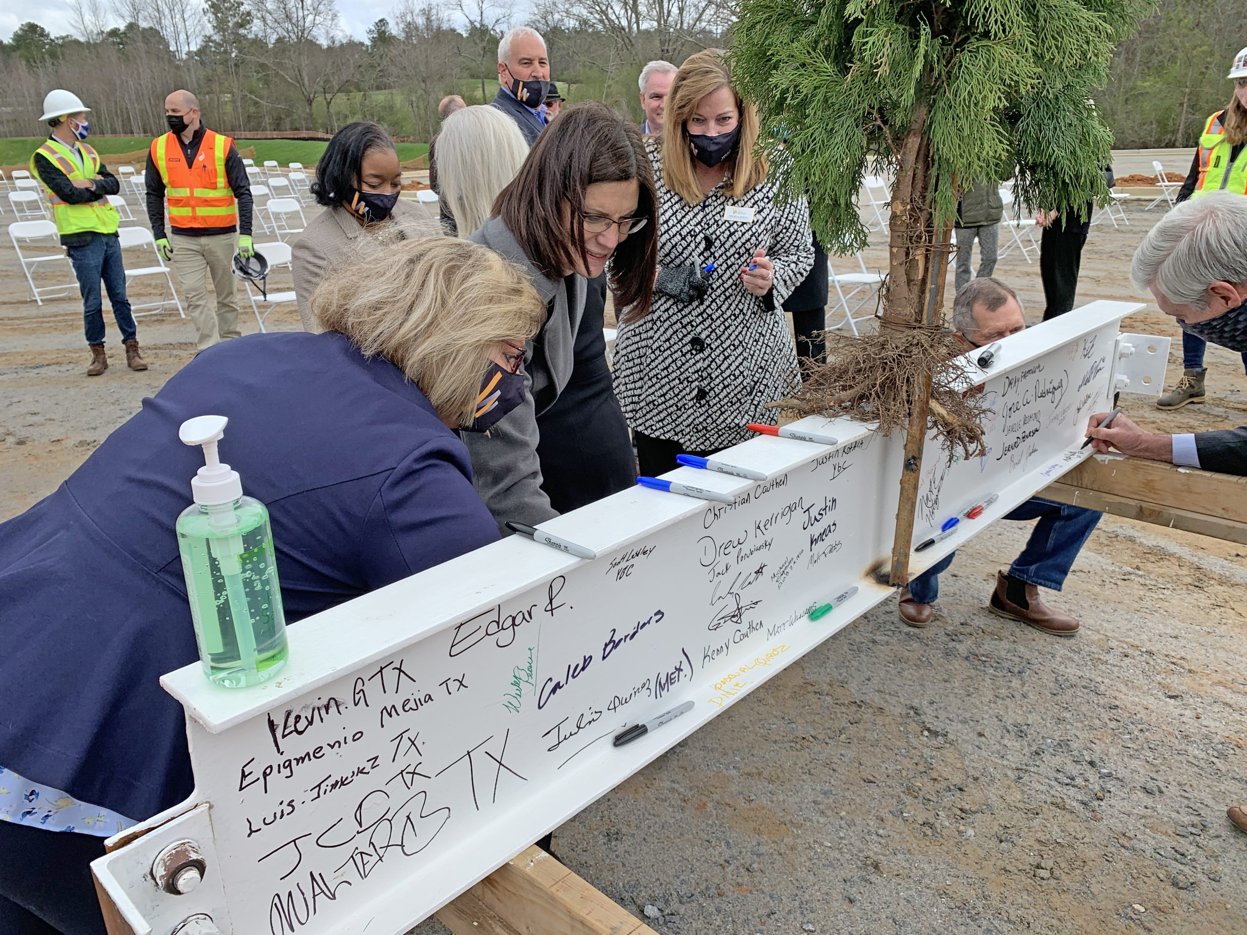WGTC staff signs beam with tree
