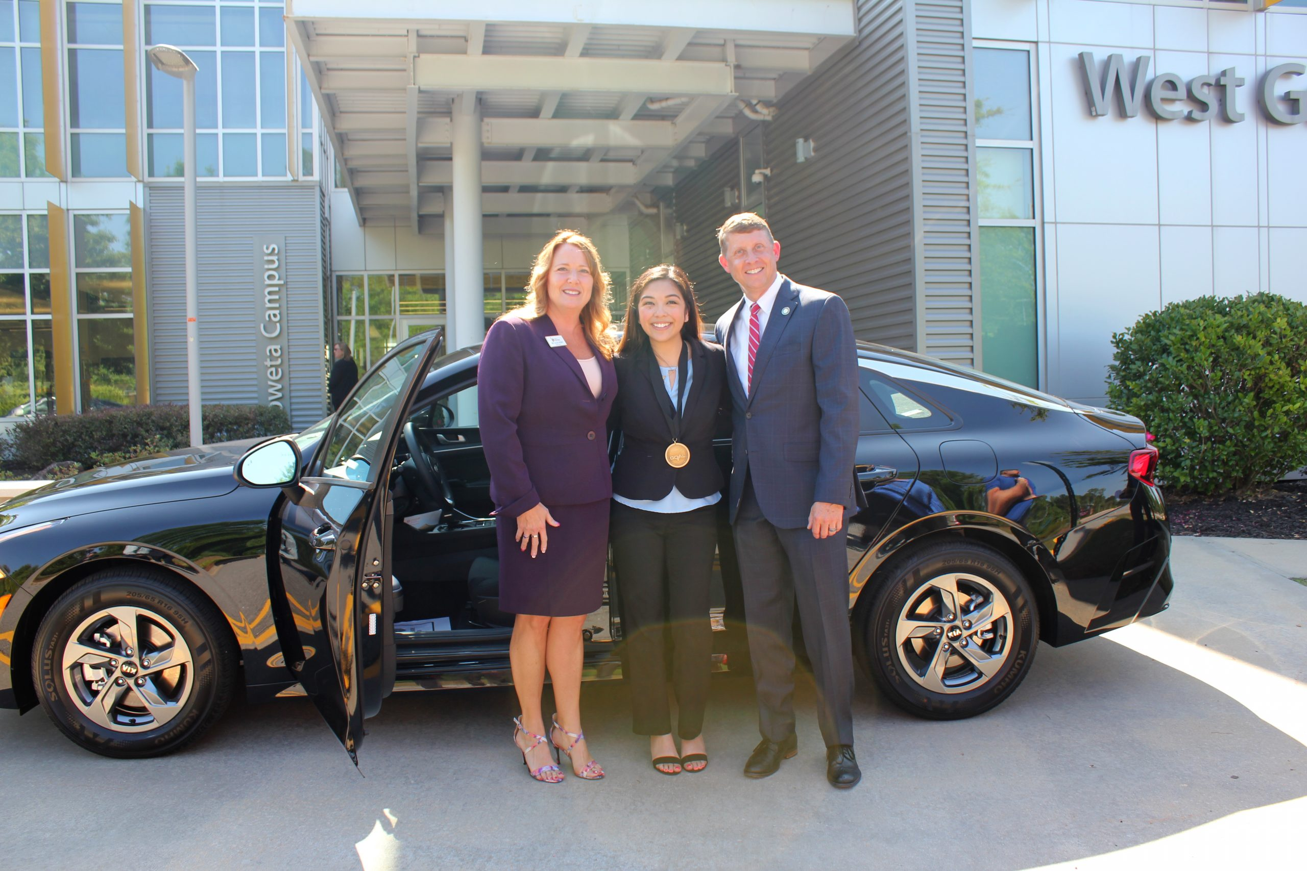 Rodriguez with president and commissioner in front of a kia
