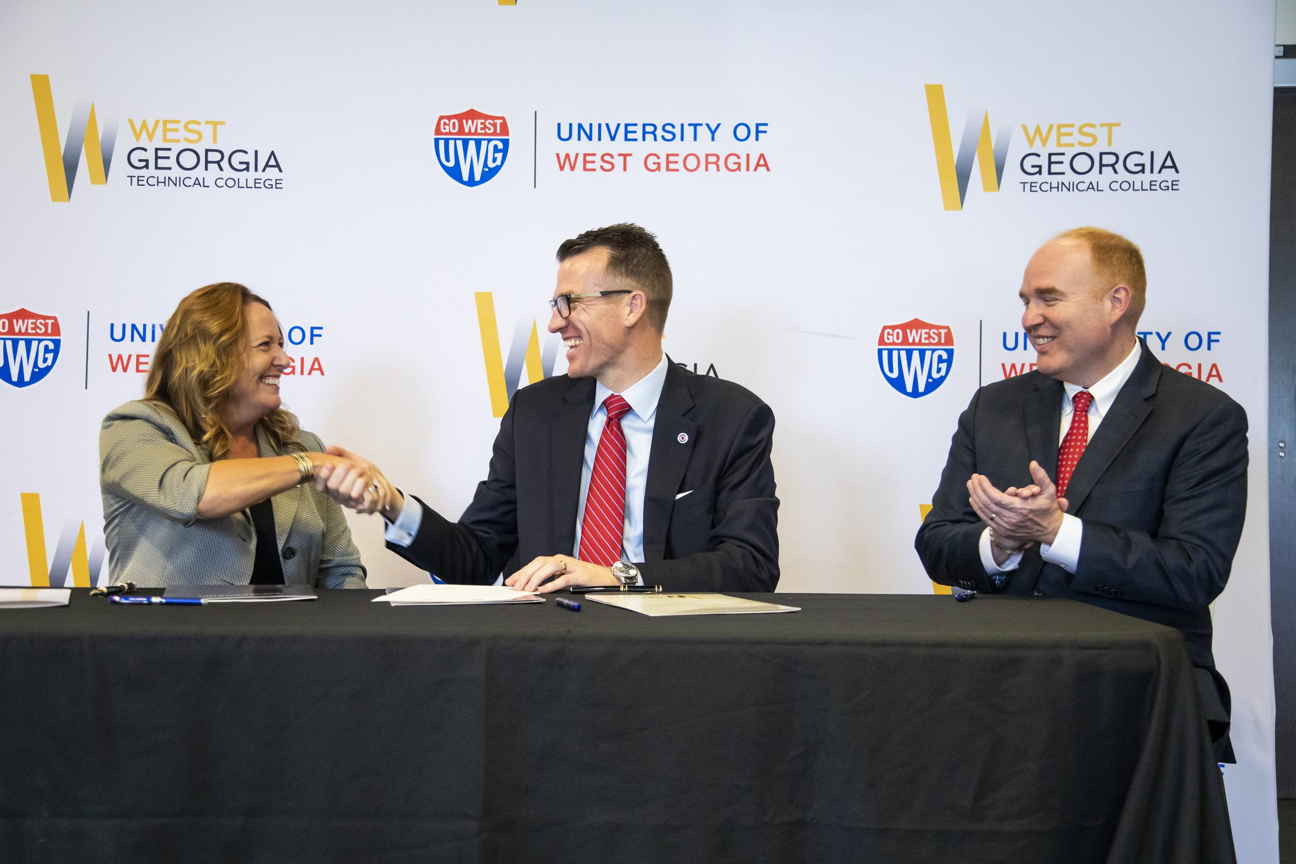 West Georgia Technical College President Dr. Julie Pos, shakes hands with University of West Georgia President Dr. Brendan Kelly as UWG's Provost and Senior Vice President Dr. Jon Preston looks on.