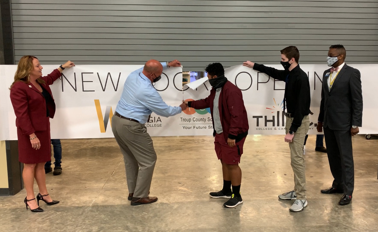 WGTC President Dr. Julie Post, Troup County Schools Superintendent Dr. Brian Shumate and THINC Academy CEO Gerald Wyatt cut through a banner separating two labs on the West Georgia Technical College LaGrange Campus.