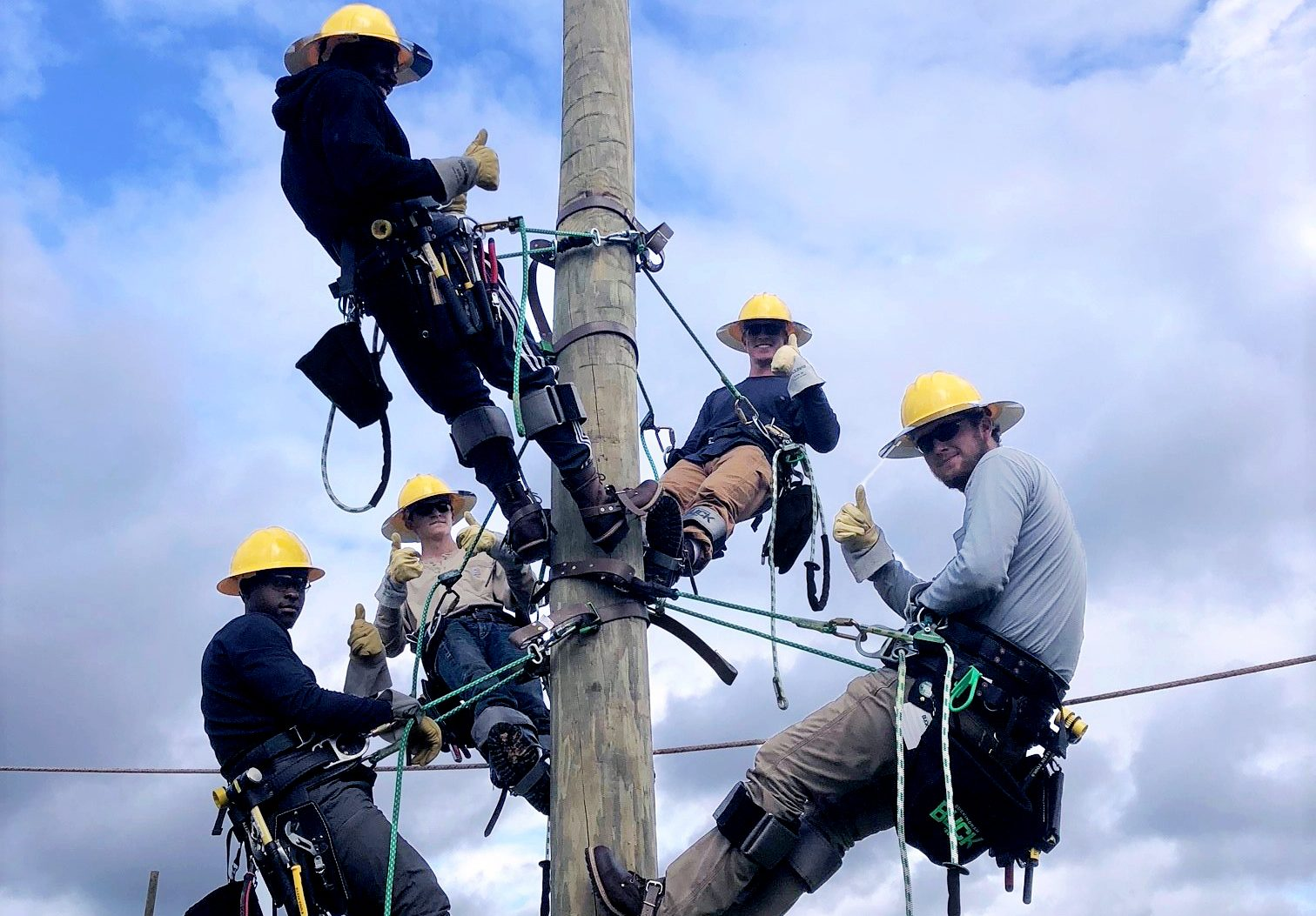 linemen on telephone pole working on power lines